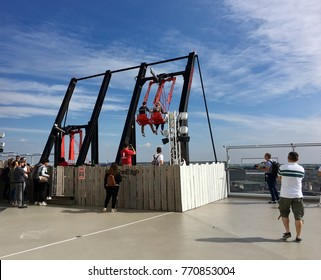 Amsterdam, Netherlands: September 04, 2017: The tourist swing at A'DAM lookout. A 20-story rooftop with a restaurant, bar and an over-the-edge swing.