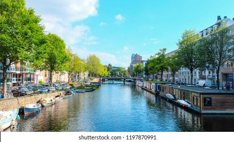 Amsterdam, The Netherlands - September 13, 2018 : View of houseboats, boats, Dutch houses, cars, bicycles and a lot of trees along the canal with clear blue sky