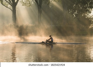 Amsterdam, The Netherlands - September 22, 2020: river Amstel on a beautiful autumn morning Rowing lady (rowing boat is a skiff), on river Amstel, fog and golden light.