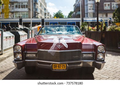 Amsterdam, Netherlands - September 23 2017: Wedding open cadillac parked on a street of Amsterdam at sunny day