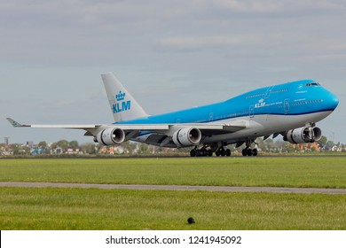 Amsterdam, Netherlands - September 28, 2018. KLM Boeing 747 Jumbo Jet shortly after touch down on Runway named Polderbaan at Schiphol Airport decelerating with thrust reverse front gear in the air