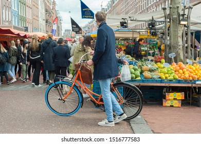 "Amsterdam, The Netherlands - September 28, 2019: Albert Cuyp market (""Albert Cuypmarkt""), Amsterdam South, bicycle (""swapfiets""), fruit stall and people."