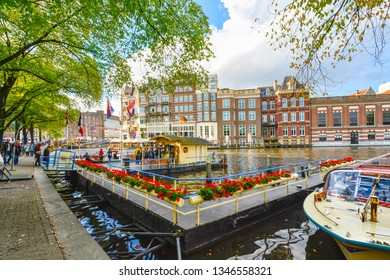 Amsterdam, Netherlands - September 29 2018: Tourists purchase tickets at a booth for boat tours on a canal in the historic center of Amsterdam, Netherlands
