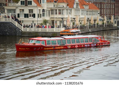 AMSTERDAM, NETHERLANDS - SEPTEMBER 30, 2017: The excursion walking boat against the background of the central tourist office in the cloudy afternoon