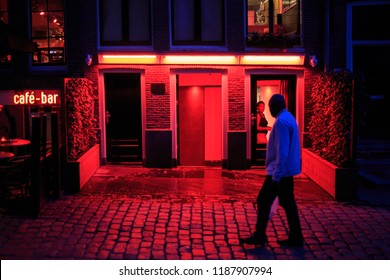 Amsterdam, Netherlands - September 4, 2018: Man walks on street in Red Light district at night