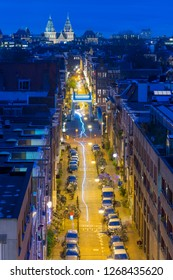 Amsterdam, The Netherlands, street with parked cars, Skinny Bridge (Magere Brug), Rijksmuseum, night shot. Light trails of traffic.