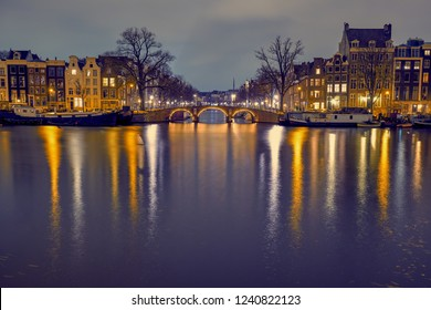 Amsterdam, the Netherlands. View of barge houses and typical old houses near the canal at night
