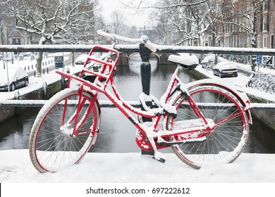 Amsterdam, The Netherlands. Winter, red bike on a bridge and canal.