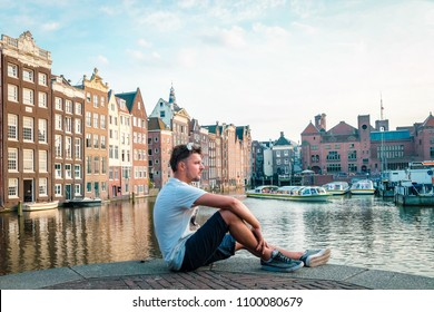 Amsterdam Netherlands Young man at Water front looking out over te canals with old historical canal house at the city of Amsterdam