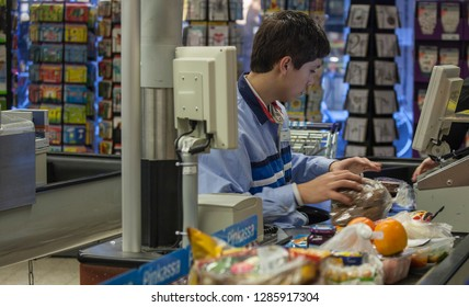 AMSTERDAM, NETHERLANDS-DEC 6, 2013: A young male cashier working in a supermarket