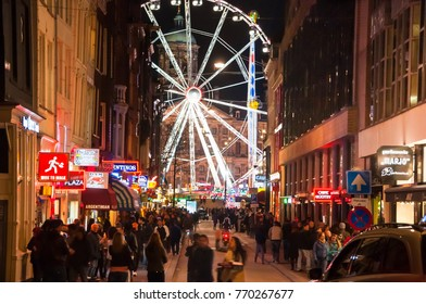 Amsterdam, the Netherlands-May 01:  Amsterdam nightlife with Dam Square and Royal Palace in the distance, amusement park full of people on May 01,2015 in Amsterdam.