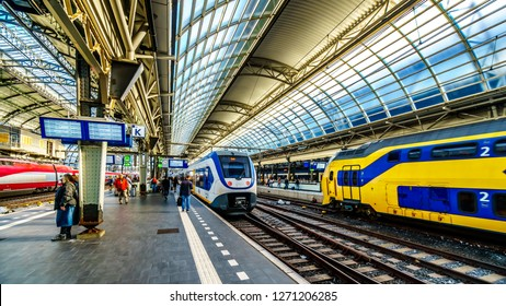 Amsterdam, Noord Holland/the Netherlands - Oct. 3 2018: Passengers waiting for their trains at the busy train station of Amsterdam Centraal