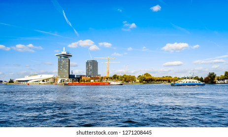 Amsterdam, Noord Holland/the Netherlands - Oct. 3 2018: The busy harbor Het IJ with the futuristicly shaped film museum 'The Eye' on the North side viewed from behind the Central Station in Amsterdam