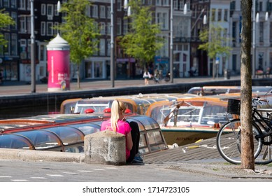 Amsterdam, North Holland / Netherlands - April 26, 2020: On a Sunday afternoon during the COVID-19 pandemic, a young woman socially isolates along the Rokin Canal in Amsterdam.
