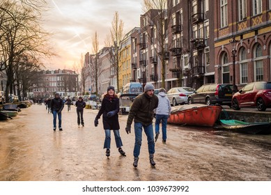 Amsterdam, North Holland / The Netherlands - March 3 2018: For the first time in 7 years, a deep freeze allows the Dutch and tourists to ice skate and walk on a frozen canal in central Amsterdam.