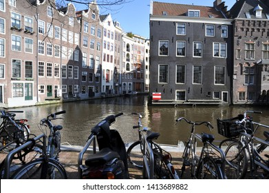 AMSTERDAM, NORTH HOLLAND / NETHERLANDS - MARCH 21 2010:  Buildings are built right up to the edge of a canal at Oudezijds Voorburgwal near red light district in central Amsterdam.