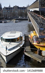 AMSTERDAM, NORTH HOLLAND / NETHERLANDS - MARCH 21 2010:  Canal boats docked next to the two-level bicycle parking lot on Stationsplein in central Amsterdam.