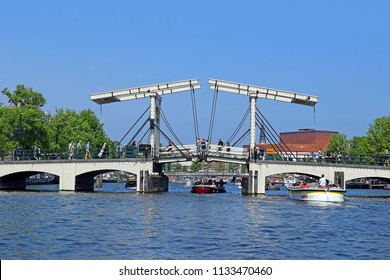 Amsterdam, North Holland, The Netherlands - May 20 2018: trip through the picturesque canals of Amsterdam. Magere Brug (Skinny Bridge) over the river Amstel in Amsterdam