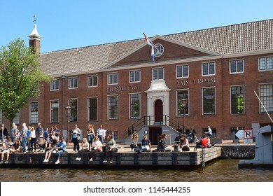 Amsterdam, North Holland, The Netherlands - May 20, 2018: tourists on the pier near the building of the Hermitage Amsterdam, branch museum of the Hermitage Museum of Saint Petersburg, Russia, located
