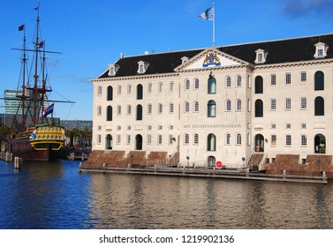 AMSTERDAM, NORTH HOLLAND, THE NETHERLANDS – OCTOBER 28 2018: National Maritime Museum, built in 1656 as a storehouse for the Admirality of Amsterdam, with a replica of the VOC ship Amsterdam