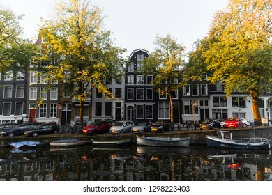 Amsterdam, North Holland / The Netherlands - October 5 2018: Morning light cast over Amsterdam canal where boat owners line their vessels ready to use any any time of the day.