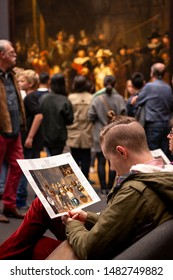 "Amsterdam, North Holland / Netherlands - October 15 2014:  Tourist reading a description of ""The Night Watch"" painting by the Dutch master, Rembrandt, at the Rijksmuseum in Amsterdam"