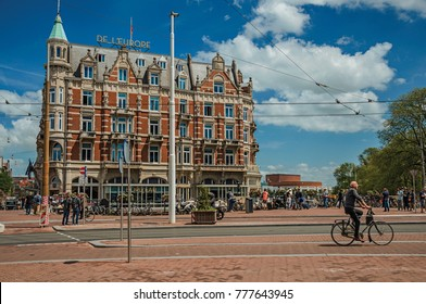 Amsterdam, northern Netherlands - June 26, 2017. Street with typical brick buildings, people and cyclists passing by in Amsterdam. Famous for its huge cultural activity, graceful canals and bridges.