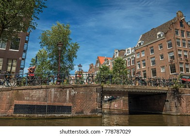 Amsterdam, northern Netherlands - June 27, 2017. Brick buildings and bridge on canal with bicycles and sunny blue sky in Amsterdam. Famous for its huge cultural activity, graceful canals and bridges.