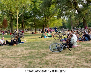 Amsterdam, North-Holland / Netherlands - 07 20 2018: The Vondelpark on a hot summer evening. People relaxing on the grass under the trees in the evening sun. Bicycles lying on the grass.