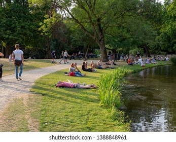 Amsterdam, North-Holland / Netherlands - 07 20 2018: The Vondelpark on a hot summer evening. People relaxing on the grass in the evening sun by the pond.