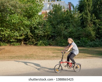 Amsterdam, North-Holland / Netherlands - 07 20 2018: Woman riding a folding bicycle in the Vondelpark in Amsterdam on a sunny summer evening.