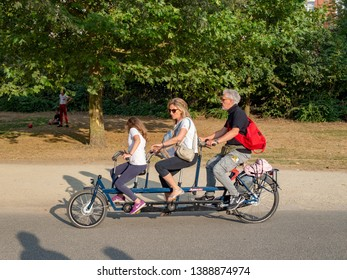 Amsterdam, North-Holland / Netherlands - 07 20 2018: Three people on a tandem bike in the Vondelpark in Amsterdam on a sunny summer evening.
