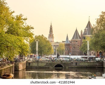 AMSTERDAM - OCTOBER 4: Clock tower of The Old Church in Amsterdam with bicycles on bridge cross canal under evening sky in Netherlands, on October 4, 2015.
