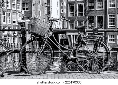 Amsterdam with old bicycle on the bridge against canal, Holland
