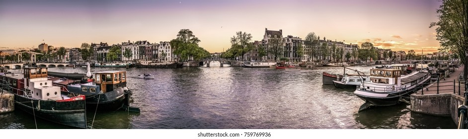 An Amsterdam panorama from Amstel river with boathouses and nice Amsterdam houses.