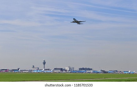 Amsterdam Schiphol Airport / Netherlands - August 28 2017: The skyline of Schiphol Airport with a passenger plane is taking off from the runway and at the background the Air Traffic Control tower ATC