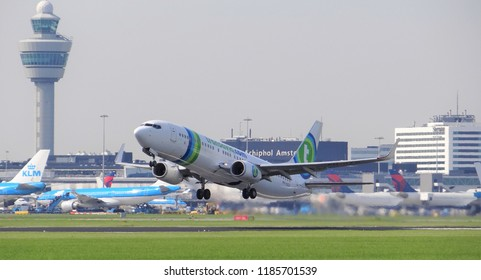 Amsterdam Schiphol Airport / Netherlands - August 28 2017: A Transavia passenger plane is taking off from the runway at Schiphol with at the background the Air Traffic Control tower (ATC)