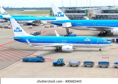 AMSTERDAM SCHIPHOL AIRPORT, NETHERLANDS - May 23, 2016. Planes of KLM Royal Dutch Airlines - Air France are preparing international flights at the platform gates and workers are delivering luggage.