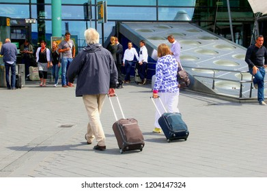 AMSTERDAM SCHIPHOL AIRPORT, NETHERLANDS - October 21, 2017. Senior couple walks outside with travel trolleys to main entrance of airport terminal, flying away for international holiday vacation.