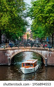 Amsterdam view - canal with boat passing under bridge and old houses. Amsterdam, Netherlands