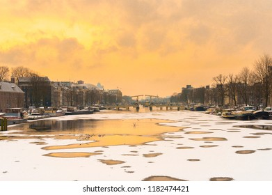 Amsterdam winter, snow and ice on the river Amstel, Skinny Bridge (Magere Brug), The Netherlands. Very cold morning, openings in the ice because of freezing wind.