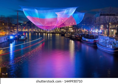 Amsterdam in winter time with beautiful lights and light trails of passing canal bus during Amsterdam Light Festival.