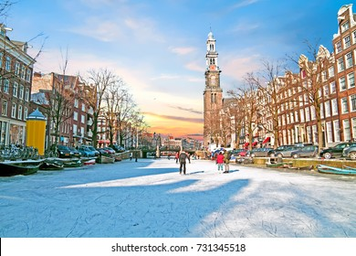 Amsterdam in winter with the Westerkerk in the Netherlands at sunset