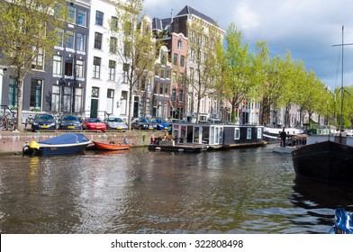 AMSTERDAM-APRIL 27: Amsterdam canal with cars and houseboats along the bank on April 27,2015, the Netherlands.