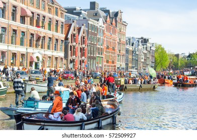 AMSTERDAM-APRIL 27: Crowd of people on the boats participate in celebrating King's Day on April 27,2015. King's Day is the largest open-air festivity in Amsterdam.Amsterdam, the Netherlands.