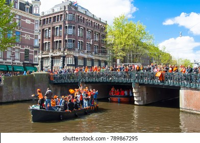 AMSTERDAM-APRIL 27:  King's Day also known Koningsdag on the Singel canal,  people look at the festival on the bridge on April 27, 2015. King's Day is held on 27 April every year.