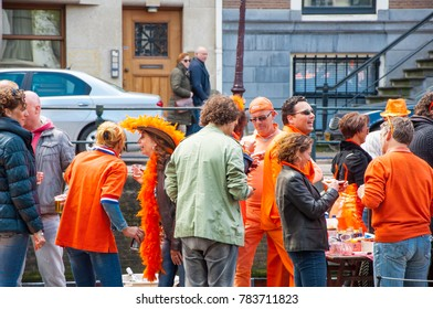 AMSTERDAM-APRIL 27: Locals in orange take part at celebration Koningsdag (King's Day) on April 27,2015, the Netherlands. King's Day festivities invite locals and visitors alike to soak up open-air fun