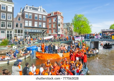 AMSTERDAM-APRIL 27: Locals and tourists on the boats participate in celebrating King's Day on April 27,2015 the Netherlands. Almost one million people arrive to the city to celebrate King's day.