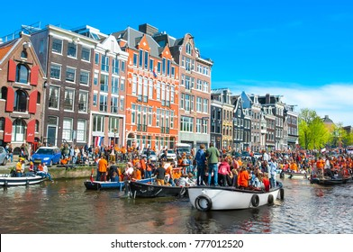AMSTERDAM-APRIL 27: People on the boats participate in celebrating King's Day through Amsterdam canal on April 27,2015 the Netherlands. King's Day is the largest open-air festivity in Amsterdam.