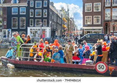 AMSTERDAM-APRIL 27:Unidentified people on the boat celebrate King's Day along the Singel canal on April 27,2015, the Netherlands. King's Day in Amsterdam is a huge orange street party.